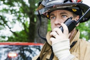 Fireman talking on public safety radio system. Mann Wireless is one of the nation's most experienced providers of custom solutions for complete, seamless coverage of public safety radio systems.