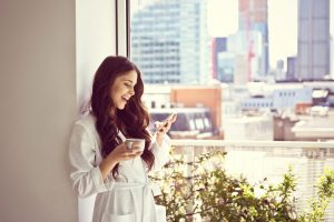 Woman in white bathrobe standing with cup of coffee in her apartment in the morning and using a smart phone, illustrating wireless connectivity solutions